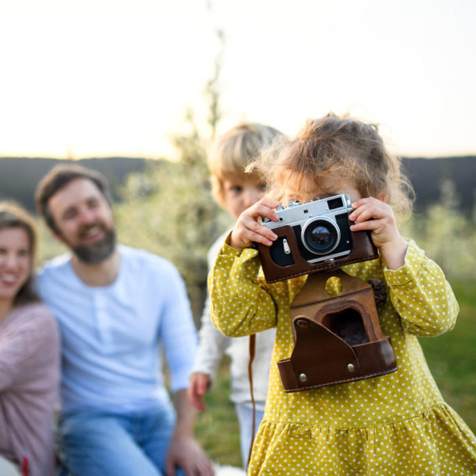 Family with two small children sitting outdoors in spring nature, taking photos.